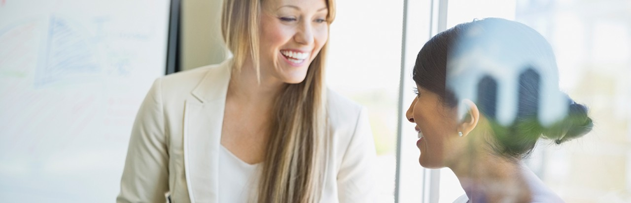 Smiling businesswomen with digital tablet talking in office